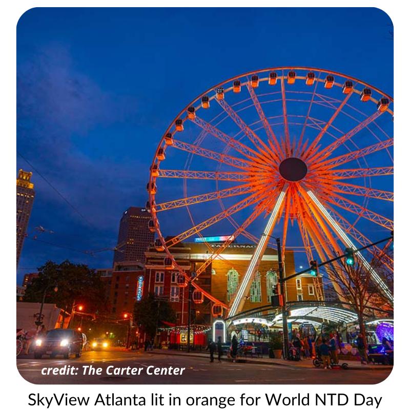 Photo of a ferris wheel illuminated in orange light